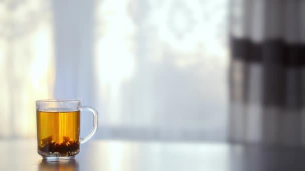 Šálek kouřící horký čaj na stole proti oknu