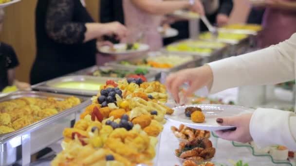 Restaurantgäste wählen Speisen vom Buffet