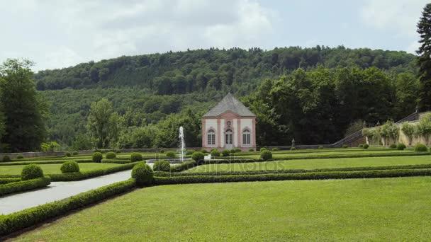 Gutshaus mit Springbrunnen auf dem grünen Rasen