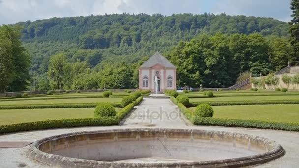 zámek s kašnou na zeleném trávníku