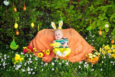 Kid sits on the lawn in the spring, Easter, bunny