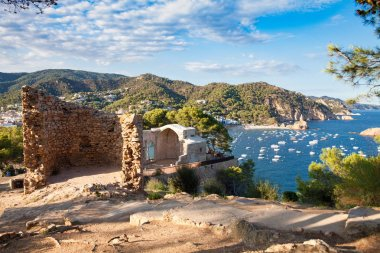 View from the castle hill towards the beach. Castle tower and fragment of walls. Tossa de Mar town on the Costa Brava, Spain. Ruins of the old town of Vila Vella.
