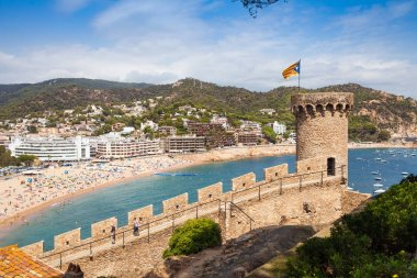 View from the castle hill towards the beach. Castle tower and fragment of walls. Tossa de Mar town on the Costa Brava, Hispania.