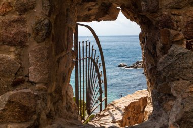 Exit to the beach by the walls of the so-called demon hole. Exit to the beach by a hollow in a wall in the town of Tossa de mar, Spain.