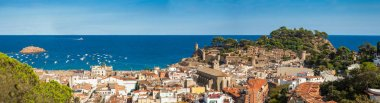 Panorama of the town of Tossa de mar one of the most beautiful towns on the Costa Brava. City walls and medieval castle on the hill. Amazing city in Girona. City, see and boats, beach with castle view.