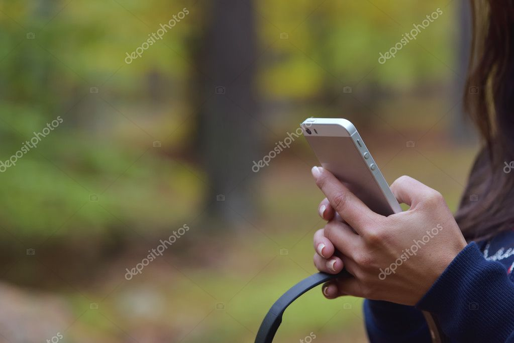 Woman holding mobile phone and headphones in hand