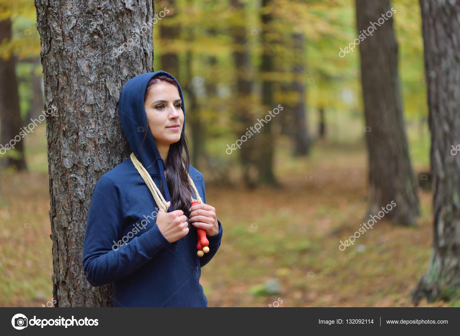 Retrato de mujer joven fit con saltar la cuerda en un parque contra colores  otoñales — 19e8ec91f0f