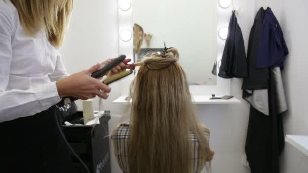 Girl hairdresser doing hairstyle.