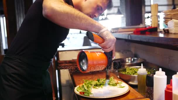 A young modern cook warms up a dish with a gas burner