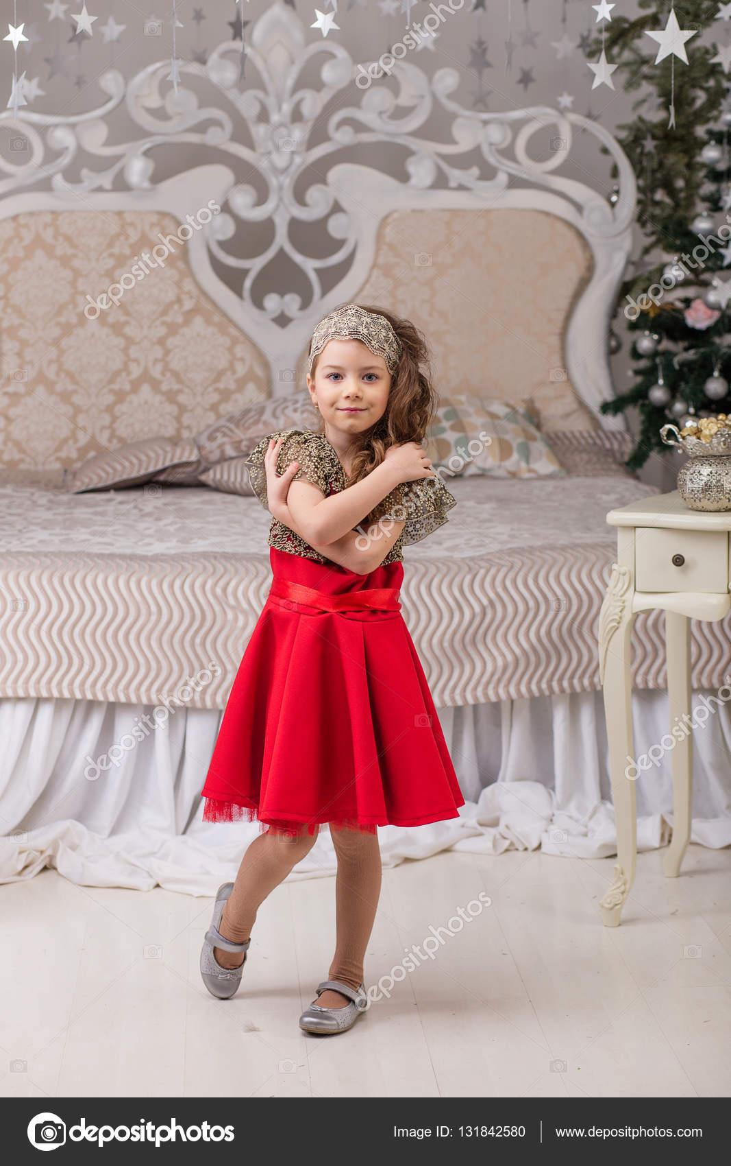 083b91d95 Niña hermosa en un vestido rojo de noche el árbol de Navidad. Chica de rojo  en adornos de Navidad. Niño lindo en la cama — Foto de  nadin1601877 gmail.com
