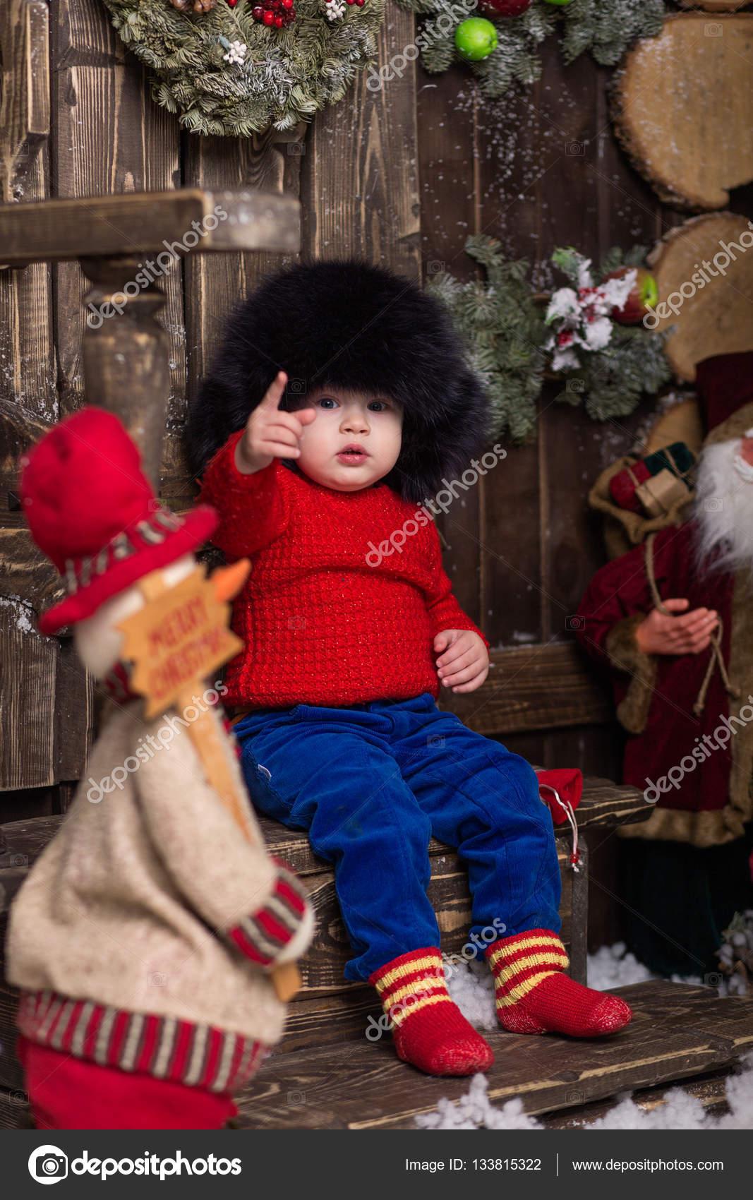 4cf412df5a8 Portrét mrňavá holka v pletená červená svetr a kožešinové čepice. Roztomilé  dítě v vánoční ozdoby — Fotografie od nadin1601877 gmail.com