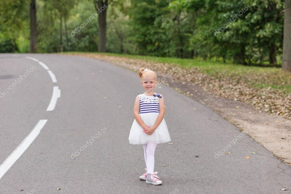 A cute little girl in a beautiful dress and sneakers playing on