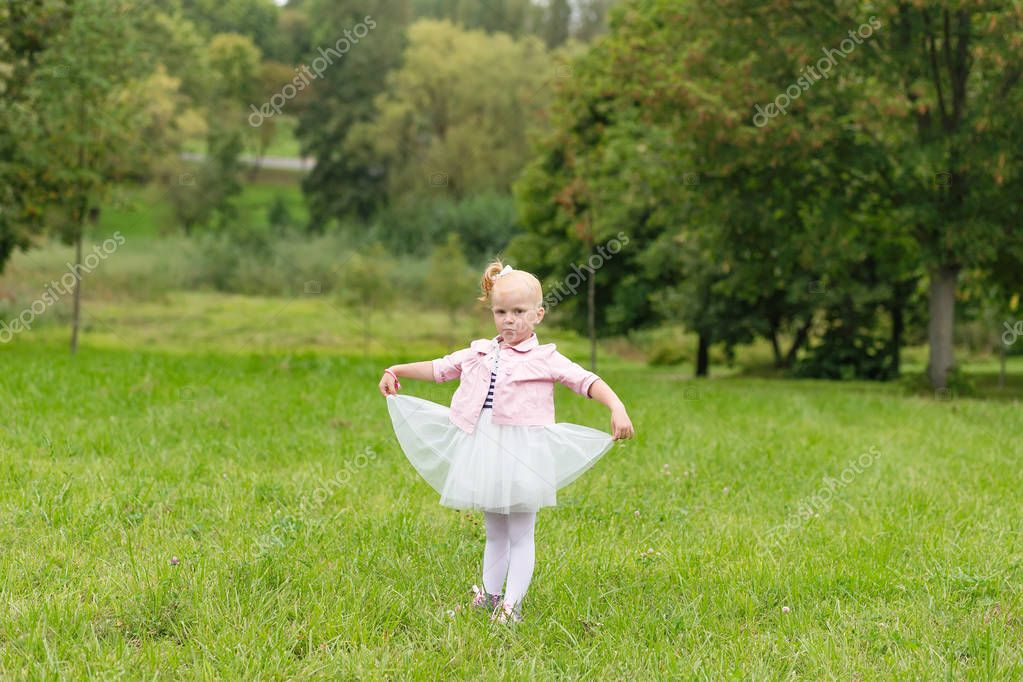 A cute little girl in a beautiful dress and sneakers playing in
