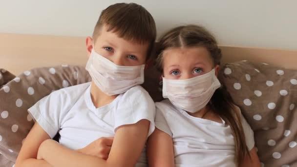 Kinder mit Atemmaske sitzen zu Hause in Quarantäne