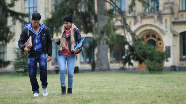 Veselí studenti tance na kampusu trávníku