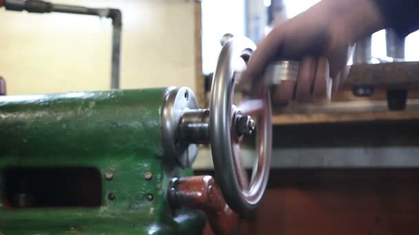 Man hand operating old controls of turning machine