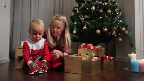 Happy children playing with toy car by Christmas tree