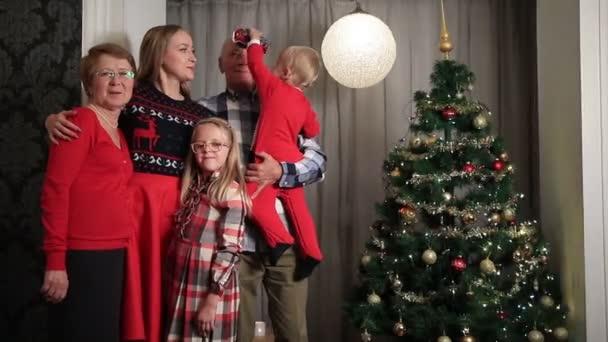 Happy family on Christmas Eve by Xmas tree