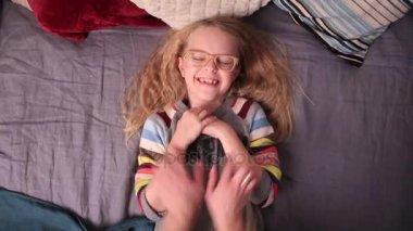 Milující matka lechtání svou holčičku na posteli