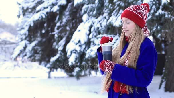 Krásná žena v zimní oblečení těší horký nápoj