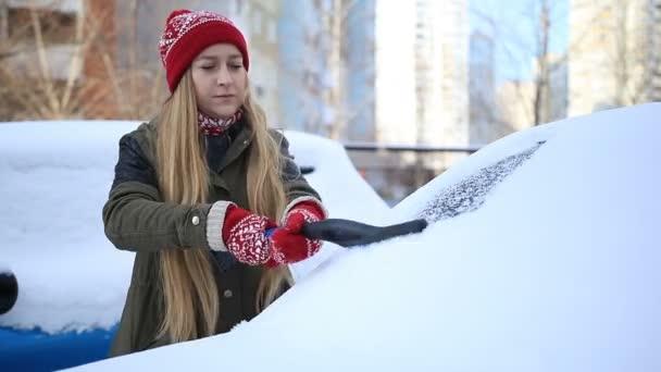 Žena, odstranění sněhu z čelní sklo auta