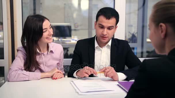 Lächelndes Paar unterzeichnet Hauskaufvertrag
