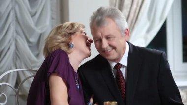 Usměvavý postarší žena šeptá manželovi