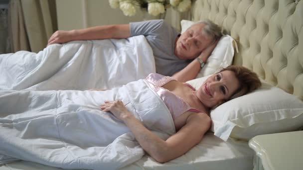 Starší žena v posteli strečink a probuzení