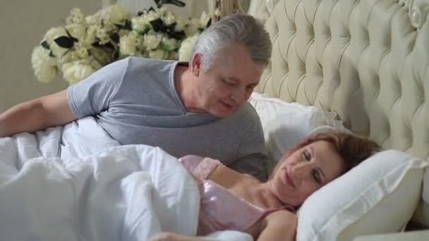Zralý pár milující lenošení v posteli po probouzející se