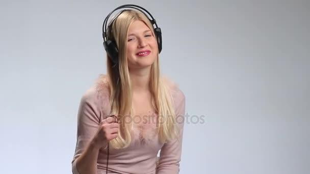 Sexy blondýnka pózuje se sluchátky