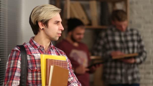 Usměvavá studentka stojící s vakem a poznámkové bloky