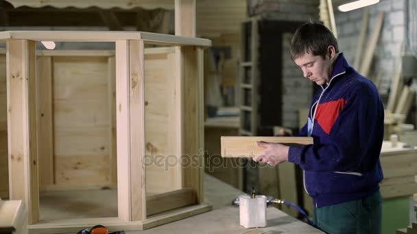 Carpenter nanesení lepidla na dřevěné prkno s kartáčem