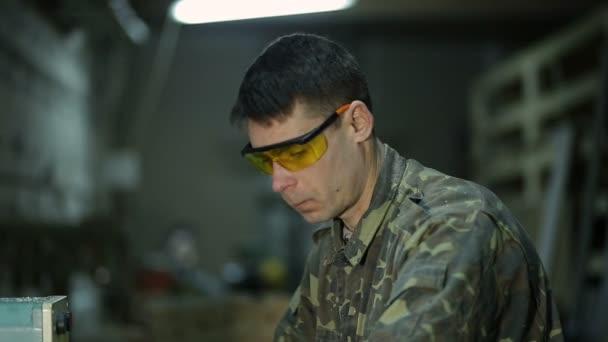 Skilled carpenter working on wood milling machine