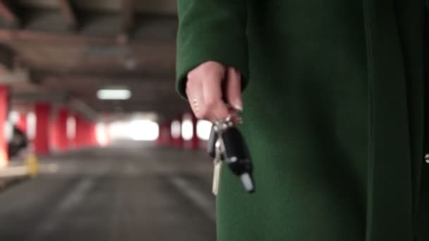 Female hand holding car key with remote control