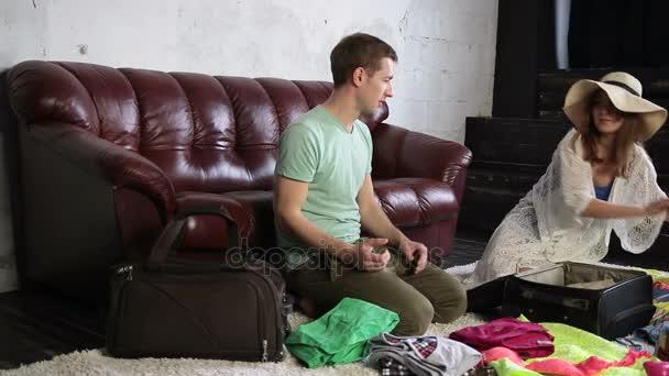 Veselý pár balení cestovní taška doma