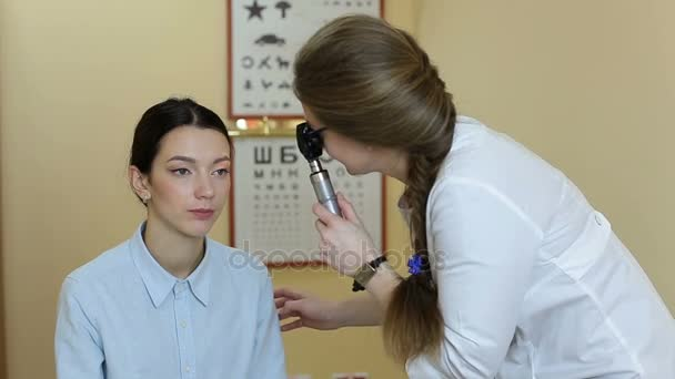 Doktor s ophthalmoscope zkoumá pacienta oči