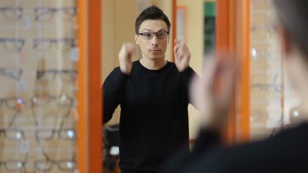Pohledný muž se snaží brýle v optické dílně