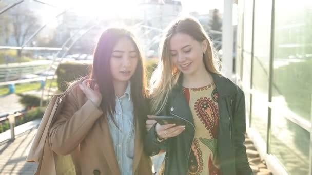 Két fiatal nők, látszó-ba okostelefonok utcában