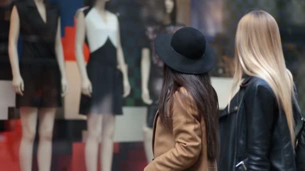 Nákupní ženy při pohledu na oblečení ukládání okna