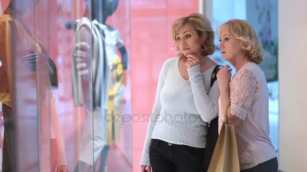 Izgatott női ruházat store ablakban nézi