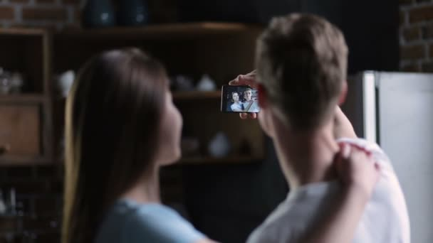 Positive couple taking selfie together at home
