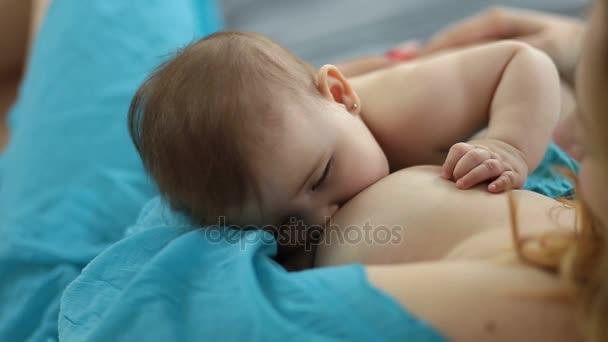 Rozkošný novorozeně je kojené matkou