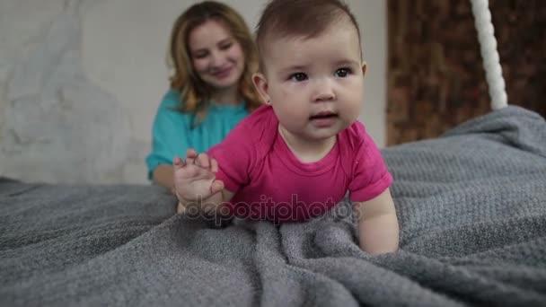 Rozkošná holčička učí lézt na posteli