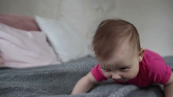 Happy baby girl crawling on bed