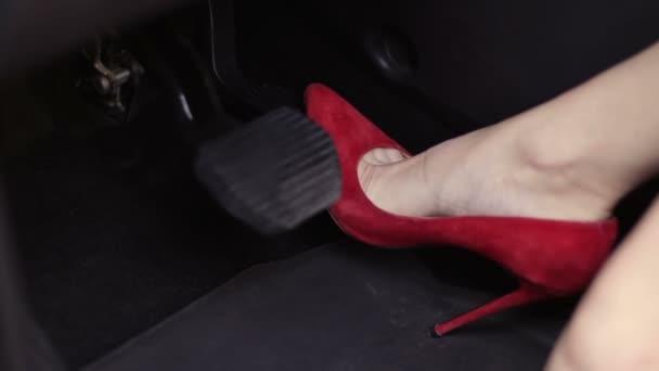 Donna in rosso i tacchi alti scarpe premendo i pedali auto