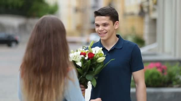Handsome man surprising lovely woman with flowers