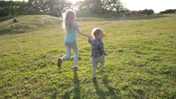 Fröhliche Geschwister rennen durch grüne Wiese