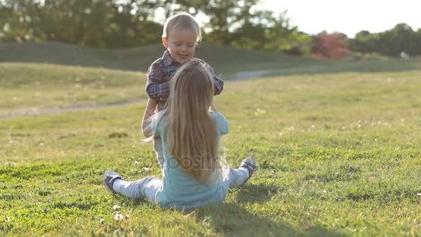 Two cute children playing together in green field