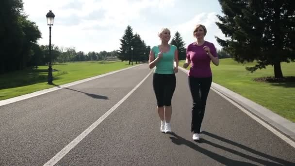 Jogging senior women running parkway in sportswear
