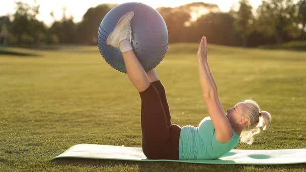Erwachsene Frau macht Übung mit Fitball im park